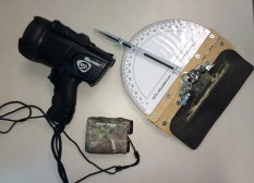 From left to right are the spotlight, rangefinder and protractor used in the survey.
