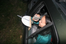 Parks staff Erin Lennon uses a laser rangefinder to find the distance, in yards, that the deer below is from the vehicle, while someone else holds the spotlight on the deer. Note the protractor mounted on the window to determine the angle.