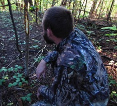 A hunter examines a deer rub, photo by Keleigh Reynolds