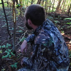 A hunter examines a deer rub, photo by Keleigh Reynolds