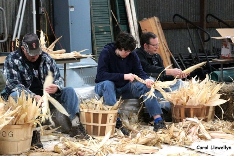 Young and old help to shuck the corn, photo by Carol Llewellyn