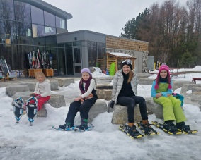 Snowshoers by the outdoor fire pit, photo by Nicandria Nature Center